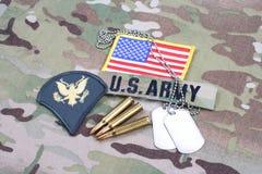 Lapp för specialist för USA-ARMÉ frodig, flaggalapp, med hundetiketten och 5 56 mmrundor på kamouflageunifor Arkivfoto