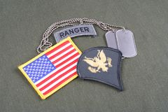 Lapp för specialist för USA-ARMÉ frodig, kommandosoldatflik, flaggalapp och hundetikett på likformign för olivgrön gräsplan fotografering för bildbyråer