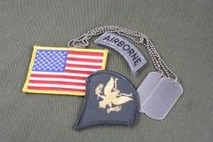 Lapp för specialist för USA-ARMÉ frodig, luftburen flik, flaggalapp och hundetikett på likformign för olivgrön gräsplan Royaltyfria Foton