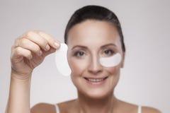 Lapp under ögon Härlig mellersta åldrig kvinna med perfekt hud som visar vita hydrogellappar med den lyftande anti--skrynkla coll royaltyfri foto