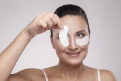 Lapp under ögon Härlig mellersta åldrig kvinna med perfekt hud som visar vita hydrogellappar med den lyftande anti--skrynkla coll arkivfoto
