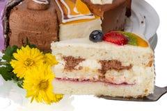 Lappa av tårtan med frukt och blommor Arkivbilder