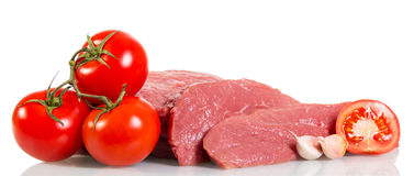 Lappa rått nötkött, tomater och vitlök som isoleras på vit bakgrund Arkivbilder