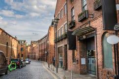 Lappad gata som fodras med tegelstenbyggnader Fotografering för Bildbyråer
