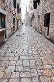 Lappad stengränd i den gamla staden av Trogir arkivfoton