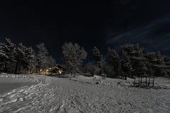 Lappish被月光照亮冬天风景,欢迎从旅馆的光在冻湖的边 免版税库存照片