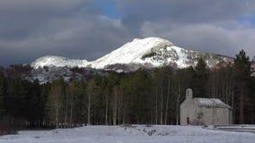 Laps de temps de montagnes d'hiver avec la vieille église banque de vidéos
