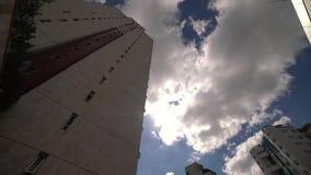 Laps de temps des nuages dans le jour ensoleillé au milieu des gratte-ciel clips vidéos