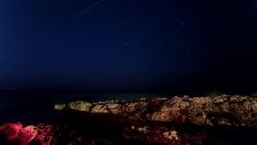 Laps de temps du ciel nocturne et des pierres rouges Là où les voiles isolées d'un bateau et une étoile tombe banque de vidéos