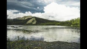 Laps de temps de jour avec la vitesse moyenne de nuages au-dessus de refléter le petit lac frais en Alaska banque de vidéos