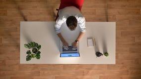 Laps de temps supérieur de tir d'ouvrier se reposant à la table regardant l'ordinateur portable et typying, mouvement de lumière, banque de vidéos