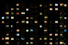 Lapso da noite da luz nas janelas de uma construção de vários andares Vida em uma cidade grande fotografia de stock