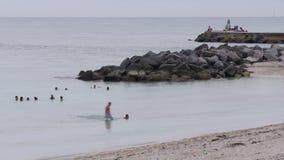 Lapso de tempo chuvoso florida dos nadadores 4k do cais da rocha da praia do verão EUA filme