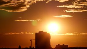 Lapso de tempo com nascer do sol sobre na cidade com construção e no guindaste no fundo video estoque