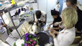 Lapso de tempo da equipe ocupada dos cozinheiros chefe que preparam o alimento em uma cozinha comercial vídeos de arquivo