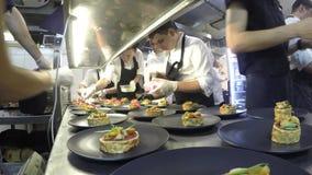 Lapso de tempo da equipe ocupada dos cozinheiros chefe que preparam o alimento em uma cozinha comercial filme