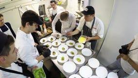 Lapso de tempo da equipe ocupada dos cozinheiros chefe que preparam o alimento em uma cozinha comercial video estoque