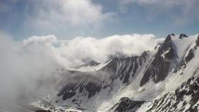 Lapso de tempo das nuvens mà intensas que roiling e que fluem sobre picos filme