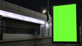 Lapso de tempo Quadro de avisos com uma tela verde, situada em uma rua movimentada Os carros movem-se na noite filme