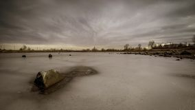 Lapso de tempo temperamental das nuvens que passam sobre um lago com as rochas no primeiro plano vídeos de arquivo
