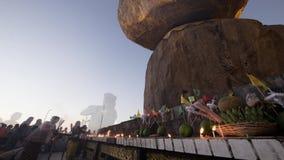 Lapso de tiempo de la gente birmana que ruega cerca de roca de oro en la puesta del sol Myanmar (Birmania) almacen de video