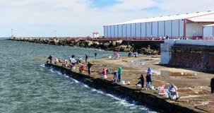 Lapso de tiempo de la gente que pesca en Escollera de Montevideo almacen de video