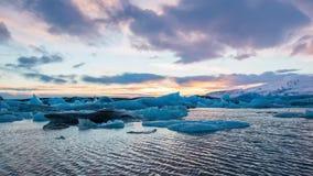 Lapso de tiempo de los icebergs azules que flotan en la laguna glacial de Jokulsarlon en la puesta del sol almacen de metraje de vídeo