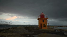 Lapso de tiempo del faro anaranjado en la noche, Islandia almacen de metraje de vídeo