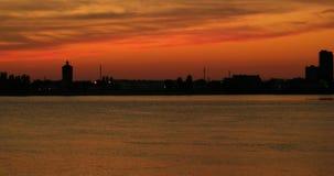 Lapso de tiempo del panorama 4k del paisaje urbano de la puesta del sol del verano Vista asombrosa del ajuste del sol en agua almacen de metraje de vídeo