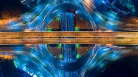 Lapso de tiempo del tráfico de ciudad de la noche en el camino del cruce giratorio del círculo de la intersección de la calle de  metrajes