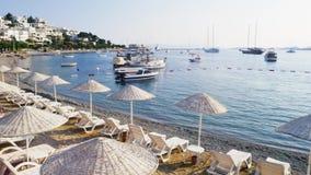 Lapso de tiempo en la costa de la ciudad de vacaciones de Bodrum, Turquía Paraguas y camas del sol en la playa Yates y barcos metrajes