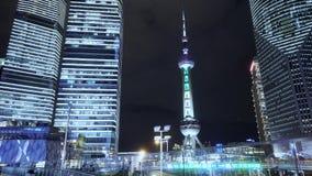 Lapso de tiempo, gente que pasa el rascacielos de Shangai y la torre de la perla TV de Oriente en la noche almacen de metraje de vídeo