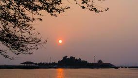 lapso de tiempo 4K de la puesta del sol en el mar con la silueta del árbol y de la isla almacen de video