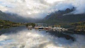 Lapso de tiempo de las nubes que remolinan alrededor de las montañas y reflejadas en la calma metrajes