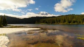 Lapso de tiempo de nubes y del cielo sobre el Mt más lluvioso con la reflexión en Washington State metrajes