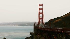 Lapso de tiempo tirado de puesta del sol majestuosa sobre puente Golden Gate icónico, igualando tráfico de coche y las flores en  metrajes