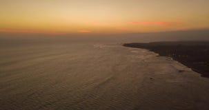 Lapso híper del abejón aéreo del cielo de oro de la puesta del sol con las siluetas de la gente que practica surf metrajes