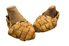 Lapti bast shoes are clad in ancient wooden shoe pads. On white background Stock Photo