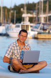 With a laptop. Successful young man with laptop at the port royalty free stock photo