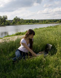 Laptop. Girl working on laptop near river Stock Photo