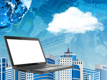 Laptop on abstract cityscape background with cloud. Virtual world map royalty free stock photo