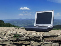 Laptop against the sky. A picture of laptop against countryside scenery Royalty Free Stock Image