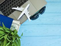 laptop airplane passport glasses plant a wooden background Royalty Free Stock Photos