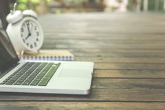 Laptop with alarm clock and notebook Stock Images