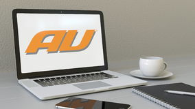 Laptop with au mobile phone company logo on the screen. Modern workplace conceptual editorial 3D rendering Royalty Free Stock Photos