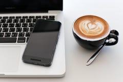 Laptop auf dem hölzernen Desktop der Weinlese im modernen Büro mit accessori Lizenzfreie Stockfotografie