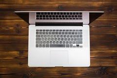 Laptop auf Draufsicht des h?lzernen Hintergrundes stockfoto