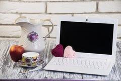 Laptop auf einem hölzernen und Ziegelsteinhintergrund Stockfoto