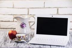 Laptop auf einem hölzernen und Ziegelsteinhintergrund Stockfotos