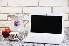 Laptop auf einem hölzernen und Ziegelsteinhintergrund Lizenzfreie Stockbilder